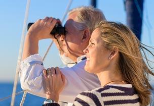 Couple sailing seeing through binoculars